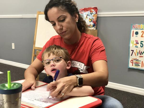 Gema Sosa helps 4-year-old Emerson White trace his name at the Creative Behavior Solutions clinic in Largo.