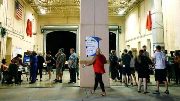 South Florida voters wait in line to cast their ballots late in the day at a busy polling center in Miami on Nov. 6, 2018.