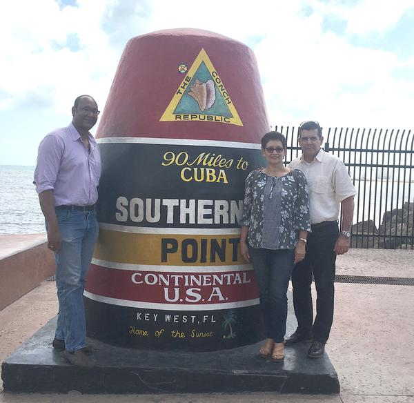 Cuban Ambassador to the U.S. José Ramón Cabañas, far right, visits the Southernmost Point in Key West Tuesday.