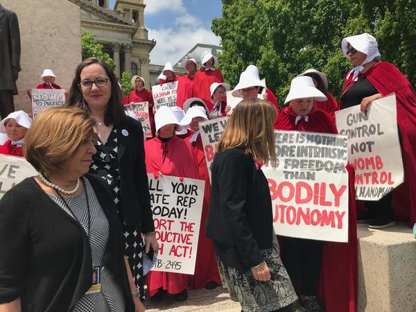 Women dressed as characters from the dystopian novel and TV series The Handmaid's Tail gather at a rally Wednesday,