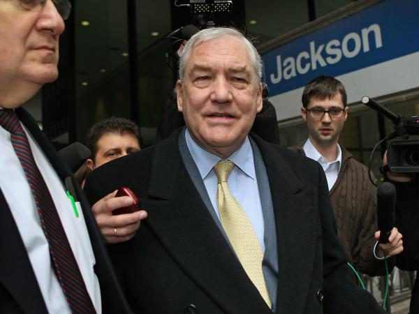 Former media baron Conrad Black was pardoned by President Trump on Wednesday. Black (center) is seen here following a 2011 hearing in Chicago.