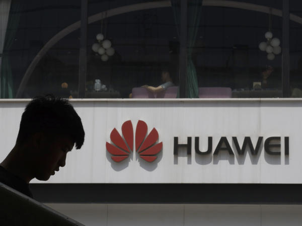 A Chinese man is silhouetted near the Huawei logo in Beijing on Thursday. The Trump administration issued an executive order Wednesday apparently aimed at banning Huawei equipment from U.S. networks.