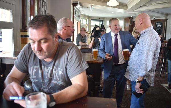 Labor party member Anthony Albanese (C) speaks to supporters over a beer in a pub in Sydney.