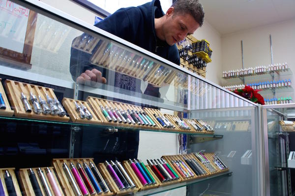 In this file video, the owner of a Spokane electronic cigarette store examines his display case.