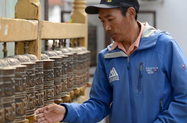 Nepali mountaineer Kami Rita Sherpa hopes to break his own record for climbing Everest, aiming for 25 summits. He's seen here in 2018, spinning prayer wheels in Kathmandu.