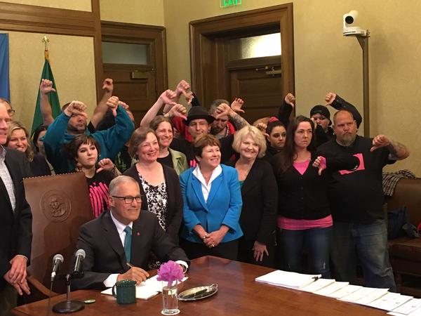 Vape shop owners give the thumbs down sign as Gov. Jay Inslee poses for a photo after signing into law a new tax on vaping liquids.