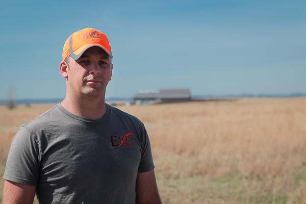 Nick Egli stands in front of the grass airstrips he's worked 10 years to establish.