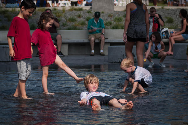 Children play in the reflecting pool in front of the Gateway Arch's visitor center on July 3, 2018.