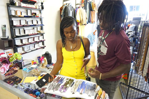 Sirena Saul looks at suits with Jason Louis, a Miami Norland senior, she took prom shopping.