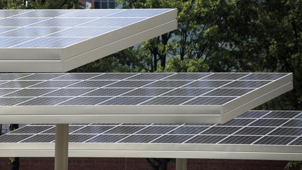 Solar panels cover cars parked in a lot nearby Centennial Olympic Park in Atlanta. The city aims to rely largely on renewable energy by 2035.