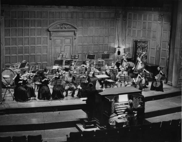 This archival photo shows a performance at Kilbourn Hall with orchestra and organ.