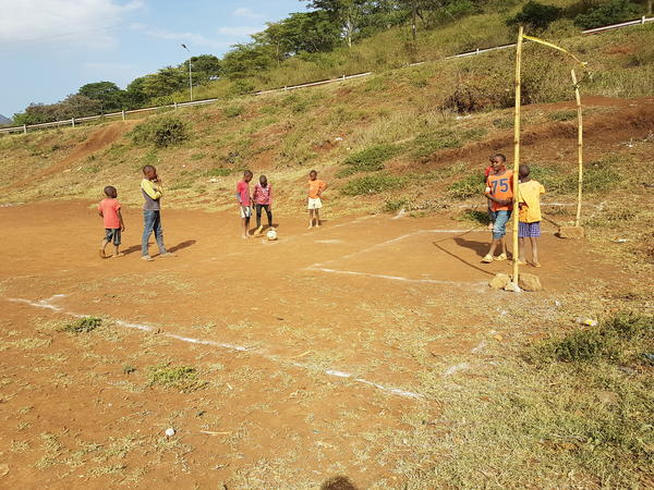 Children in the village of Arusha, Tanzania on a dirt soccer field