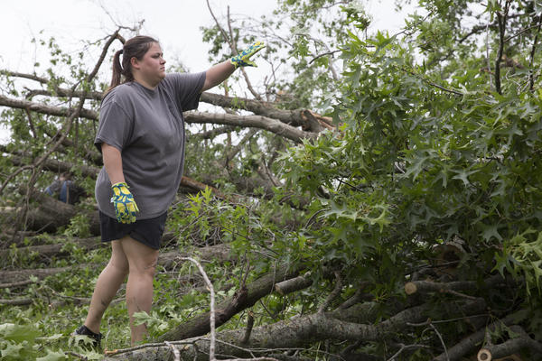 Katelyn Bossolono clears debris from her yard after the tornado that chewed through Linwood, Kansas.