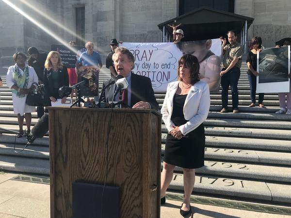 Senator John Milkovich, center, and Representative Valeria Hodges, right, hold a press conference on the steps of the Capitol following the final passage of Senate Bill 184.