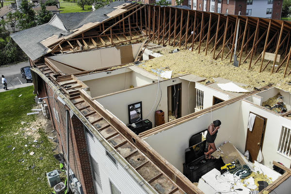 Residents sort through apartments open up to the air Tuesday, May 28, at the Westbrooke Village Apartments in Trotwood, Ohio, after the roof was torn off from a severe storm the night before.