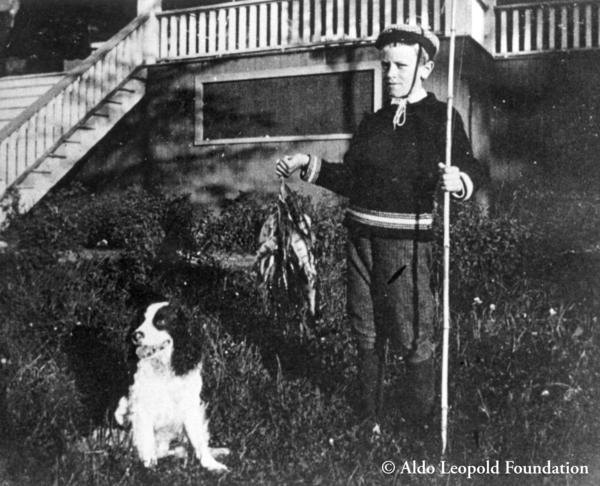 A young Aldo Leopold and his dog Spud with fish at Les Cheneaux, ca. late 1890s.