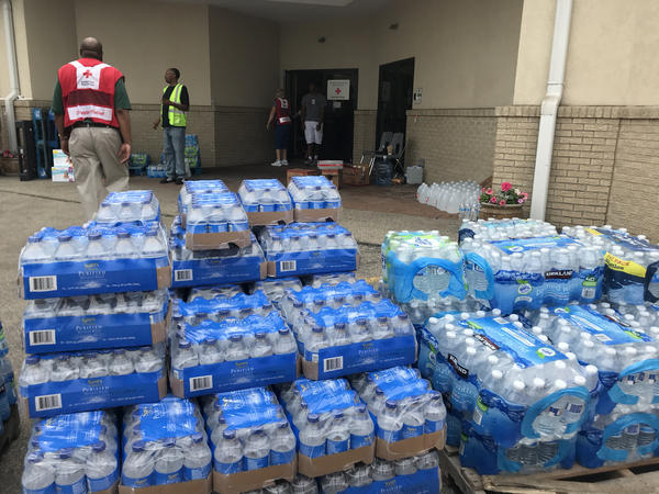 Donated water bottles are stacked in front of the Corinthian Baptist Church.