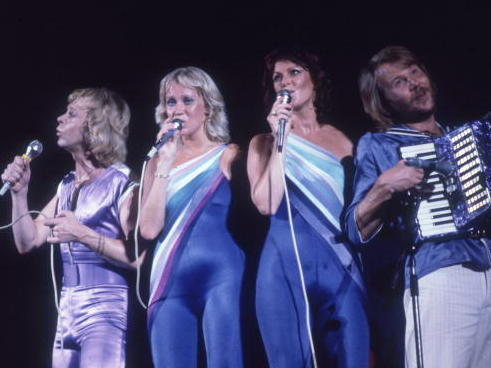 The Swedish musical group ABBA performs onstage in 1979, all wearing blue and lavender spandex outfits.