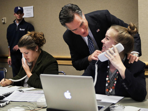 Republican presidential candidate Mitt Romney speaks with a staffer on the night of the Florida primary in January. Now that he's pivoting away from the primaries to the general election, Romney is expected to quadruple his staff soon.