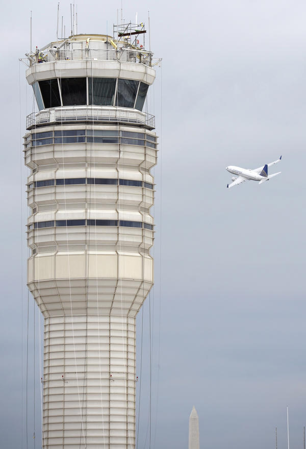 A passenger jet flies past the FAA control tower at Washington's Ronald Reagan National Airport in 2011.