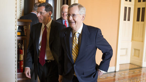 Sen. Mitch McConnell (right) walks with Sen. John Barrasso to a news conference about the compromise Tuesday.