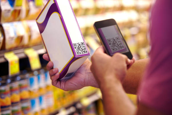 A man scans a voucher code in with his smartphone. Some food companies use labels like this to provide details about ingredients and manufacturing processes to consumers.