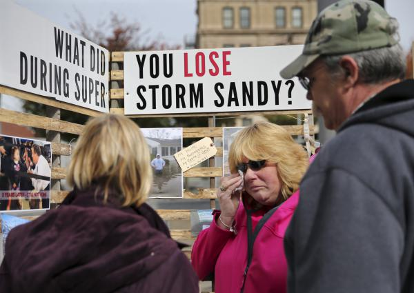 Sue Kenneally (center) wipes tears as she and other victims of Superstorm Sandy gather during a demonstration across from the statehouse in Trenton, N.J., in October 2015. More than three years after the 2012 storm, many residents are still not back in their homes.