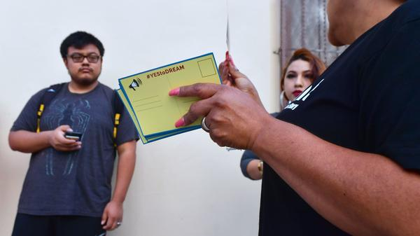 Volunteers offer cards to be filled out and sent to members of the House of Representatives as Deferred Action for Childhood Arrivals (DACA) recipients wait in line at the Coalition for Humane Immigrant Rights (CHIRLA) office in Los Angeles on September 30, 2017.