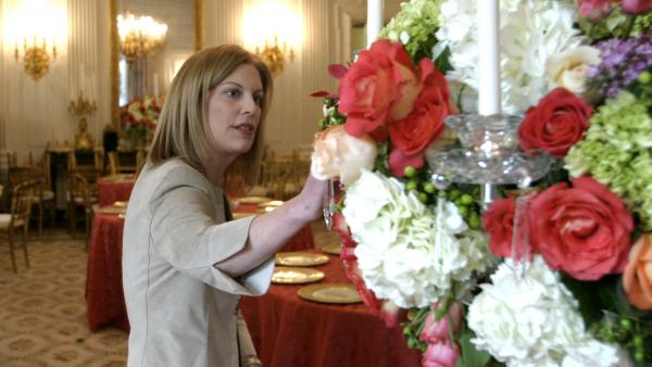 Lea Berman, White House social secretary for President George W. Bush, looks over flower arrangements in the State Dining Room before a state dinner for U.S. governors.