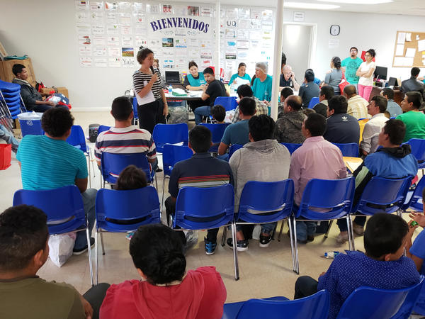 About 100 newly arrived immigrants listen to a volunteer walk them through the process to seek asylum at a Catholic Charities respite center in McAllen, Texas.