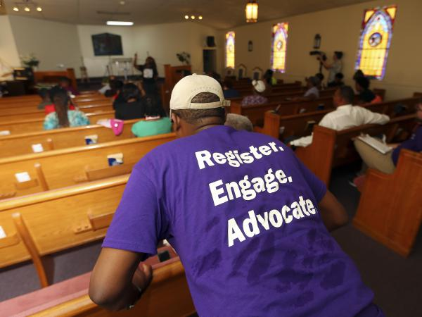 Faith-based groups from both sides of the political spectrum are working to inspire voters for the midterms. A man listens as Black Voters Matter co-founder LaTosha Brown speaks at a church as part of The South Rising Tour, aimed at getting more voters to the polls.