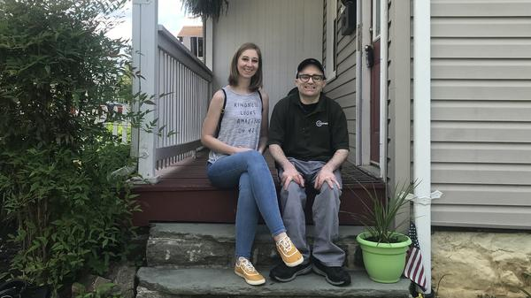 Ashley Merson and her brother Kevin sit on the porch of the house Ashley is trying to buy in the Hampden neighborhood of Baltimore. A ransomware attack on the city's digital services has delayed the home purchase.