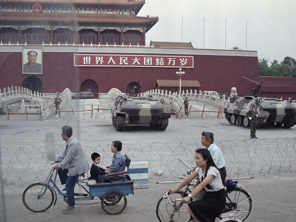 People ride bicycles on a street through Tiananmen Square on June 13, 1989, as the Chinese Army guards the square where students rallied for democratic reforms.