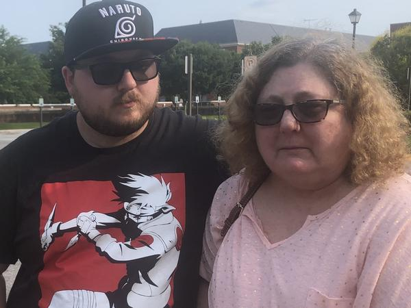 Christi Dewar, a survivor of the Virginia Beach mass shooting, stands with her son, Charles Dewar III, next to the office complex where a gunman killed 12 and injured several others on Friday.