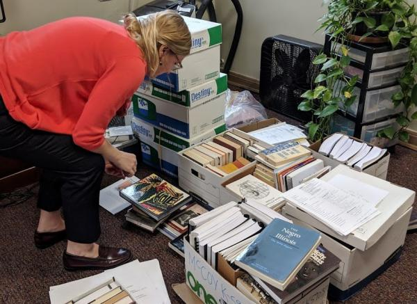 Holly Clingan, a volunteer librarian for the Education Justice Project looks through books that were removed from the program's library inside the prison. The books are currently located on the U of I campus.