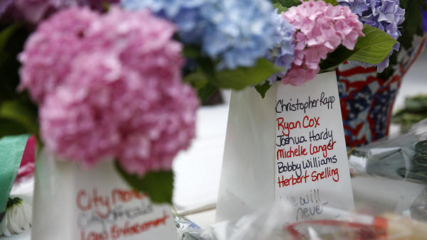 Victims' names cover part of a flower vase at a makeshift memorial for victims of a mass shooting at a municipal building in Virginia Beach, Va., on Sunday.