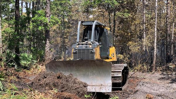 A bulldozer plows through the dirt to create a fire line and restrict the Yellow Bluff Wildfire from spreading on Thursday, May 23, 2019.