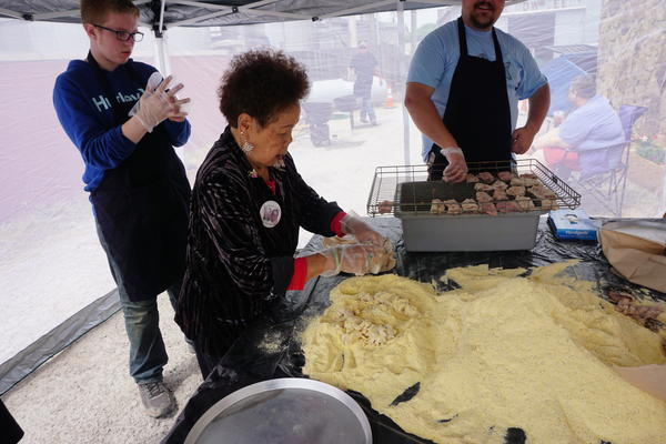 Volunteers coat sucker fish fillets with a secret recipe before putting them into the fryer at Nixa Sucker Days.