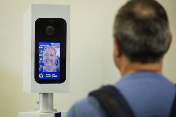 Boston resident looks into the camera for a facial recognition test before boarding airplane.