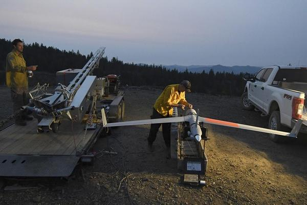 <p>Ty Sibley, right, an unmanned aircraft system operator for Insitu, prepares a ScanEagle drone on a ridge south of Galesville Reservoir near Azalea, Ore. on Aug. 7, 2018.</p>