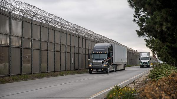Cargo trucks pass the secondary fence that divides the United States and Mexico in Otay Mesa, Calif., on May 31. Vice President Pence held a meeting with Mexican officials on Wednesday over threats to raise tariffs on that country.