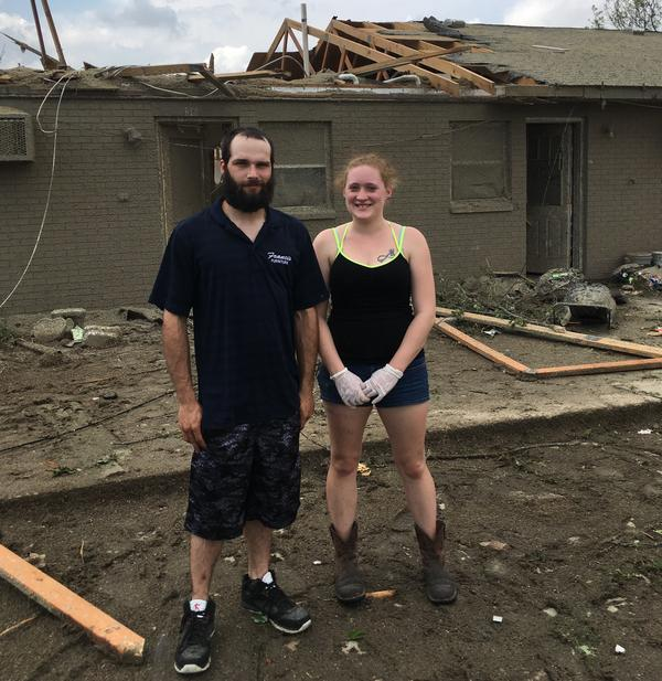 Jakob Wenning and Marissa McNelly stand in front of their tornado-damaged apartment.