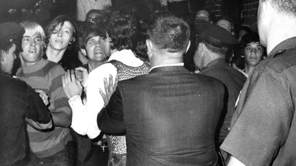 The crowd attempts to impede police arrests during the raid on the Stonewall Inn nightclub, June 28, 1969.