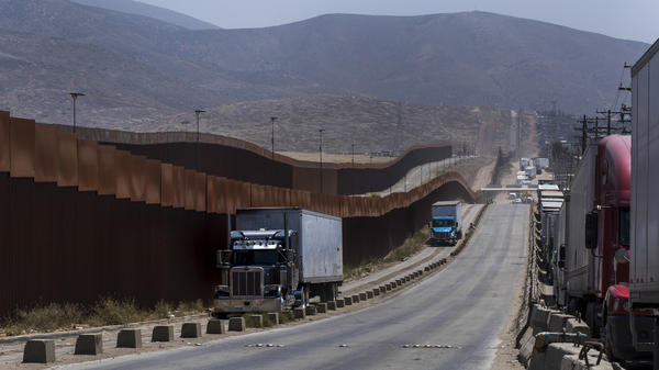 Trucks pass along a border wall as they get into position to cross into the United States at the border in Tijuana, Mexico, on Friday. Companies had been rushing to ship as many goods as possible out of Mexico to get ahead of possible tariffs threatened by President Trump.