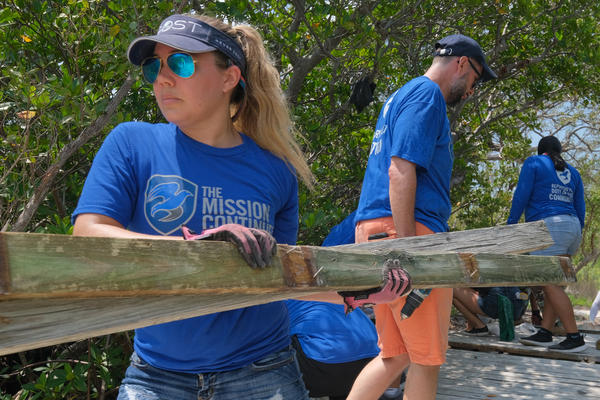 Veterans and their families demolish a wooden foot bridge in Biscayne National Park.