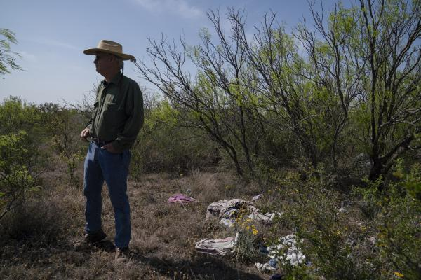Hugh Fitzsimons stands next to a pile of debris migrants left behind once they crossed into the United States.