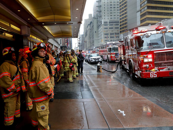 Firefighters respond to the scene where a helicopter crash-landed on the roof of a midtown Manhattan skyscraper on Monday.