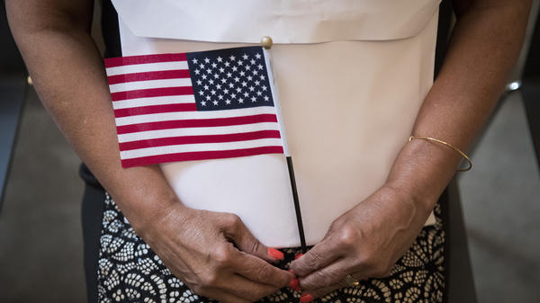 A participant in a 2018 naturalization ceremony holds a U.S. flag in New York City. Research by the Census Bureau suggests the citizenship question is highly likely to scare households with noncitizens from taking part in the constitutionally mandated head count.