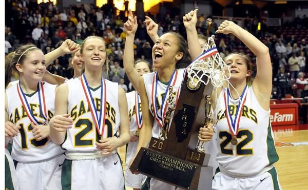 St. Thomas More's Courtney Wax holds the Sabers' first-place trophy after the team, including from left, Andie Bolton, Lauren Croft and Taylor During, far right, won the IHSA Girls' Basketball 2A State Championship in 2014 at Redbird Arena.
