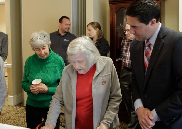 Secretary LaRose (right) showing a resident the new machine at National Church Residences in Columbus.